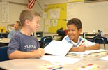 Two young boys in classroom with worksheet