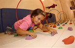 Elementary girl climbing a rock wall in gym